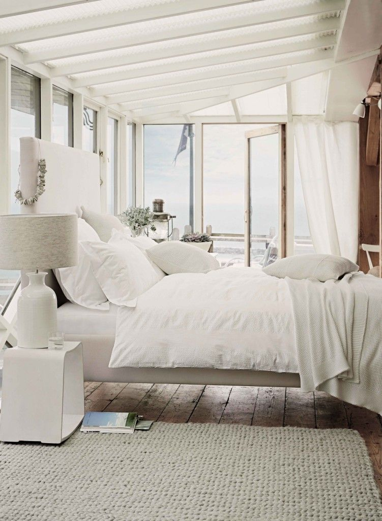 Spacious and snow white bedroom is literally immersed in the light  thanks  to many windows. Bold Country Style Bedroom Design