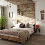 Wooden head of a bed in small bedroom