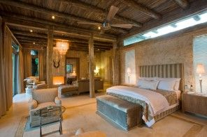 Original country-style bedroom with wooden ceiling, decorative antlers and wide bed