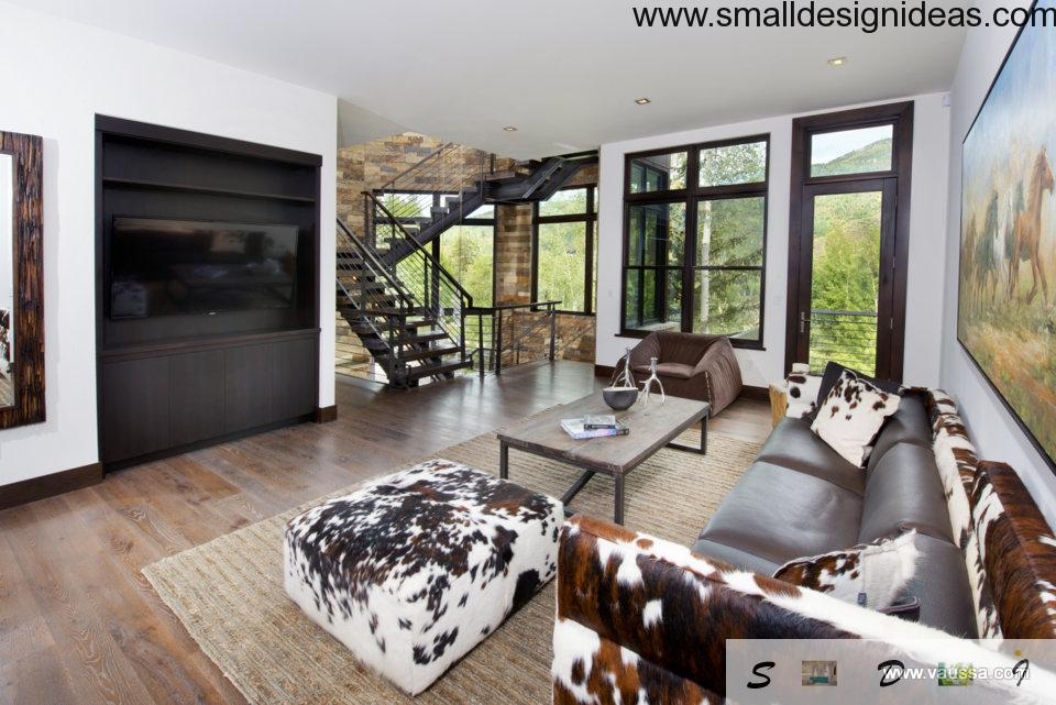 Natural colors and materials in a rustic countryside living room with built-in fireplace and black massive metal stairs