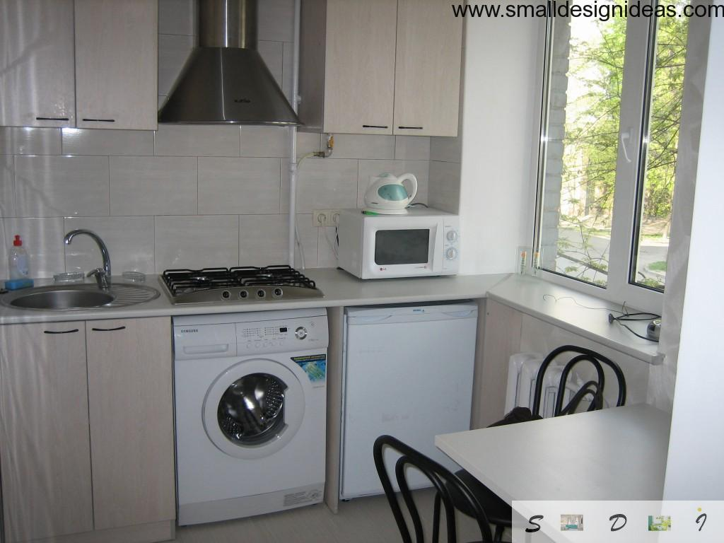 washing machine snug fitted into the small kitchen design with dining zone