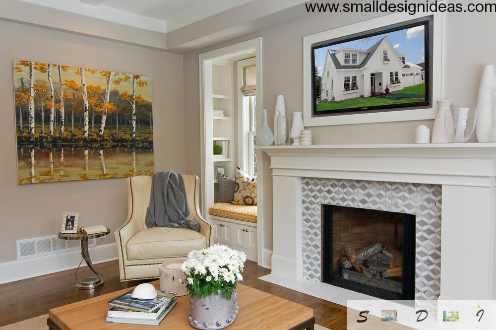 White fireplace in the living room decorated with painting and flowers