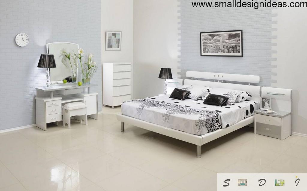 White bedroom design with contrast of black pillows and painting frames