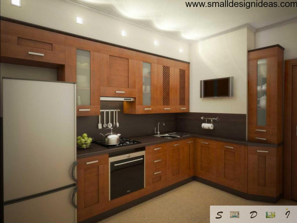 Oak furniture and white technics and walls at the l-shaped kitchen interior design