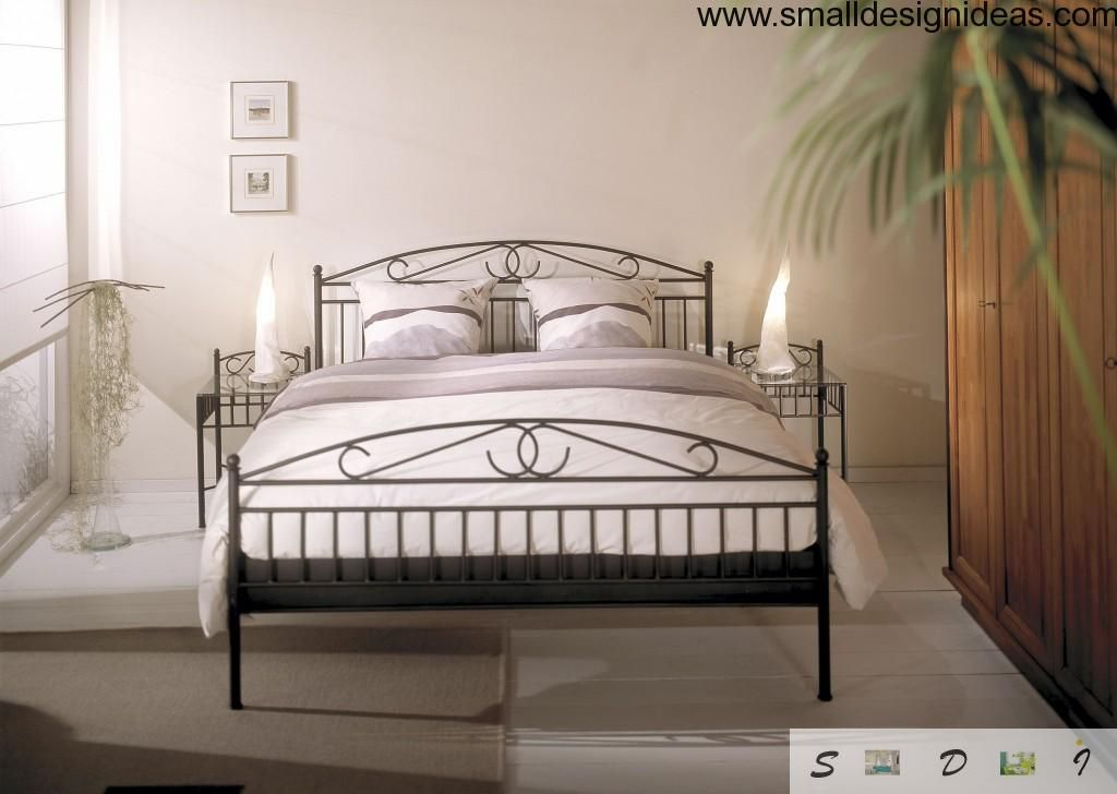 Black forged bed in the interior of white bedroom