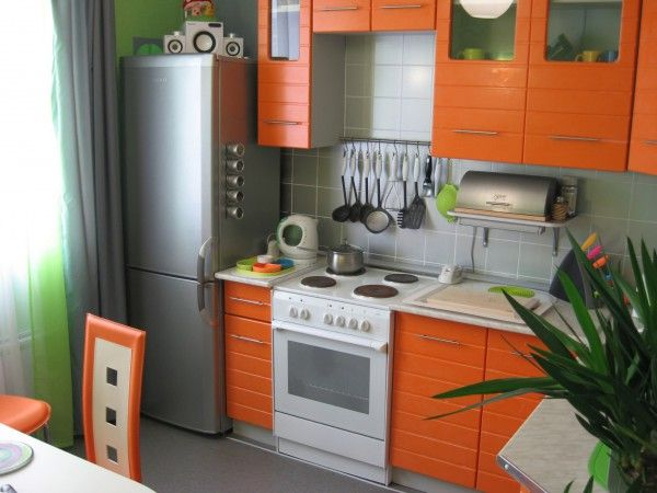 Bright perky orange design of small kitchen with plants