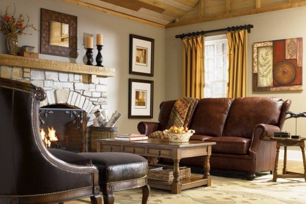 Classic English style interior: hearth, leather furniture with carved wooden basis, coffee table, a lot of pictures, cornices and tapestries