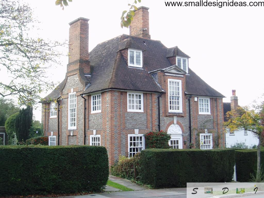 Aristocratic English house of three floors, white window frames, dark brown roof tile, two chimneys and trimmed  shrubs in the yard