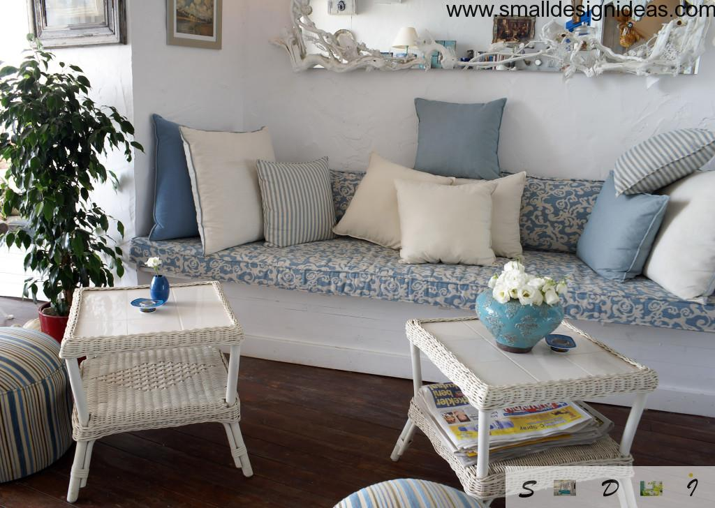 Calm and fresh rural Provence style in the interior with marine blue motifs and a lot of pillows on the couch