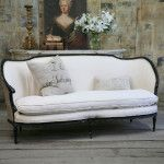Classic vintage furniture and decorations with vase, candlestick and picture as the background of the cozy white textile couch
