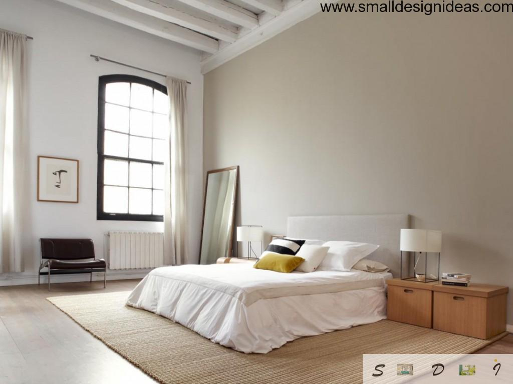 High ceiling in the Loft bedroom of New-York apartment with minimum of furniture and floor-placed mirror
