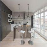 Kitchen with a lot of metal details and with grey and steel decoration, wooden glass grid to the balcony at the Loft kitchen