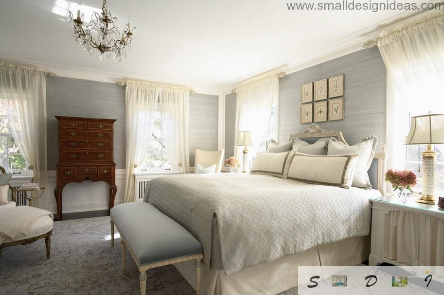 wooden chest of drawers as a contrasting element of the classic bedroom interior in light tones