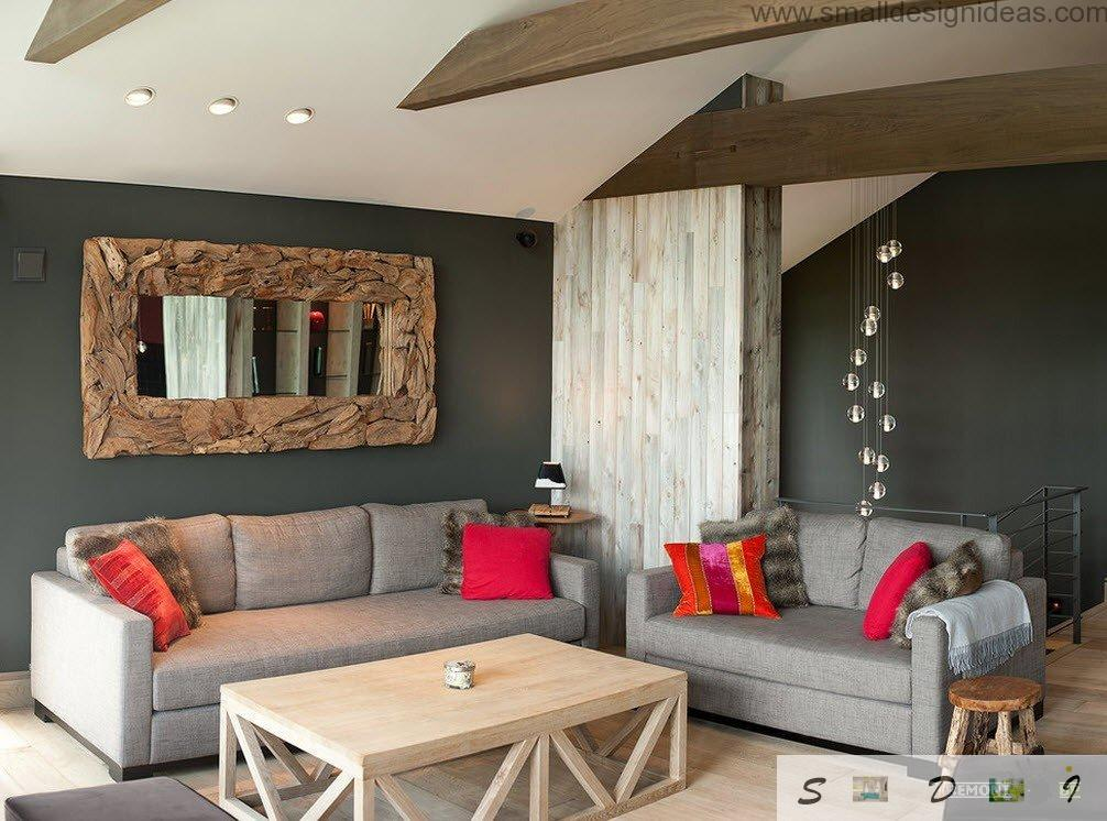 Small red cushions of the uphosltered furniture in the living room makes the atmosphere