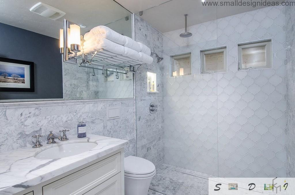 Ideally white bathroom with textured tile walls, terry clothed towels and a sink