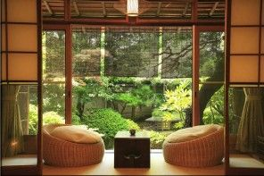 Veranda of the country house in the Japanese style with rattan puffs and low table