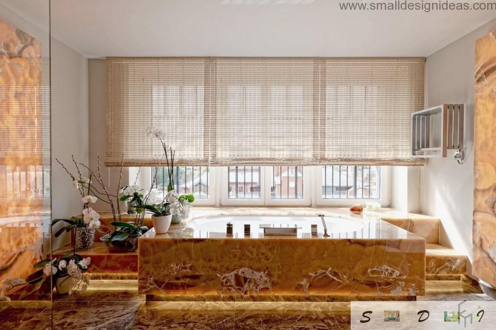 Unique marble trimmed bathtub and Venetian blinds at the huge window in the bathroom
