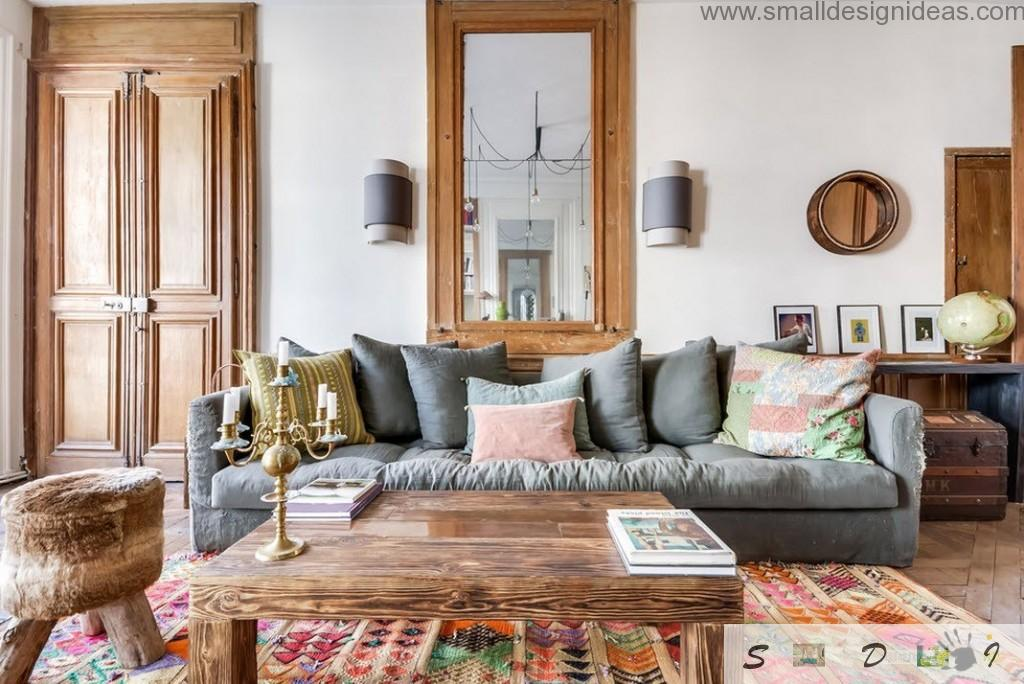 mirror in a wooden frame and cozy upholstered sofa with contrasting in the white interior cushions as the design idea