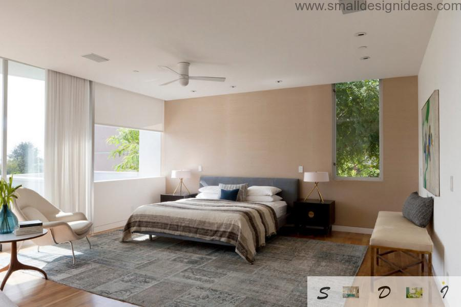 Creamy walls and white ceiling with spot lights contrasting with dark notes of carpet and bed linen