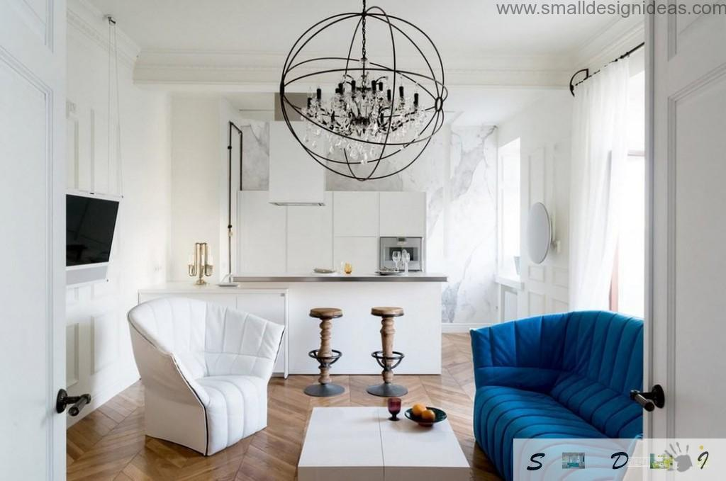 Blue upholstered sofa on a steel frame in the focus of big living room decorated with unusual spherical chandelier and bar stands