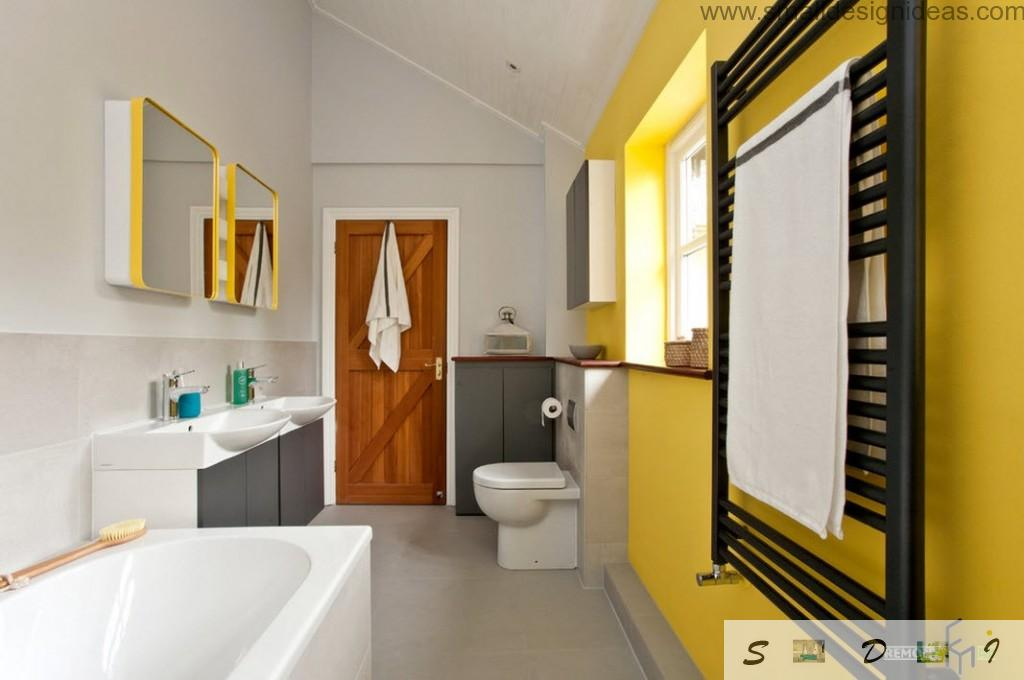 Yellow colour and mirror adds joy into the bathroom interior