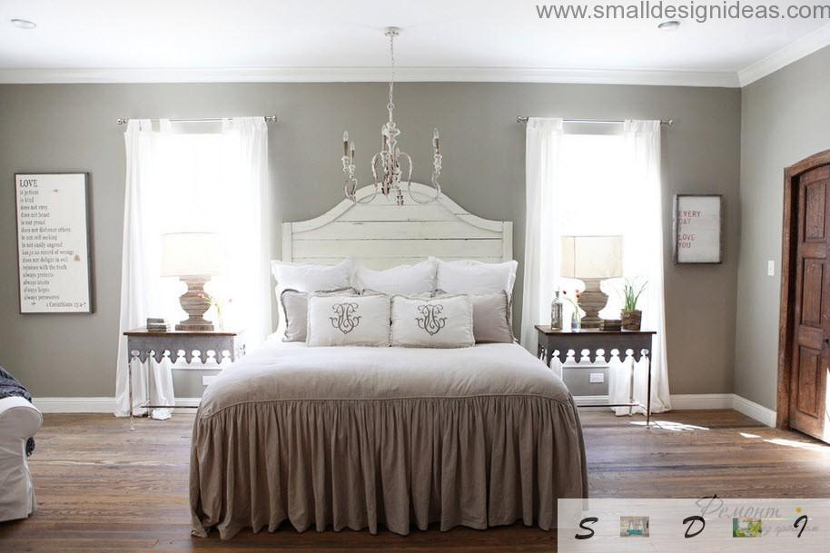 Fringed bed in milk coffee tones with large wooden headboard in the classic design interior