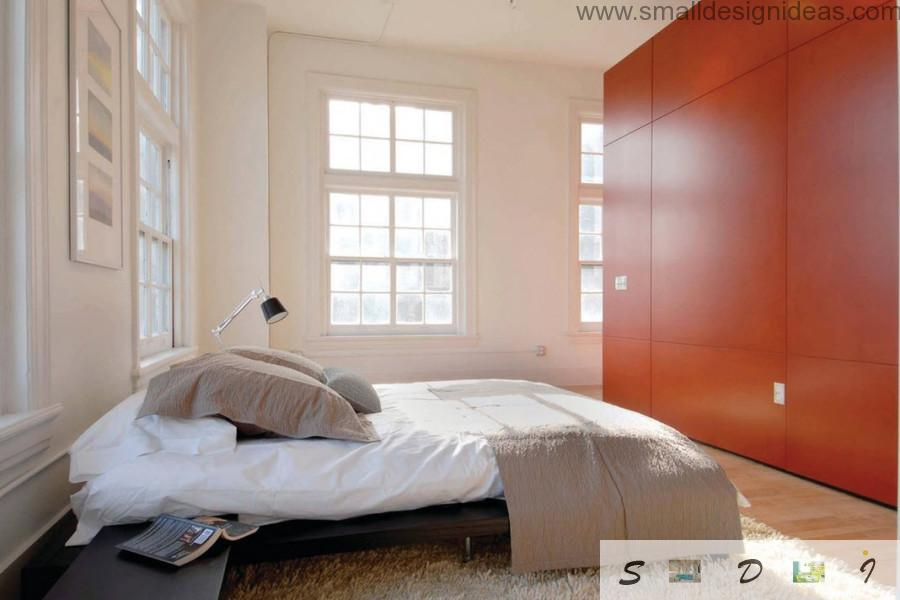 Bright wooden wardrobe in the bedroom adds vivacity to the interior