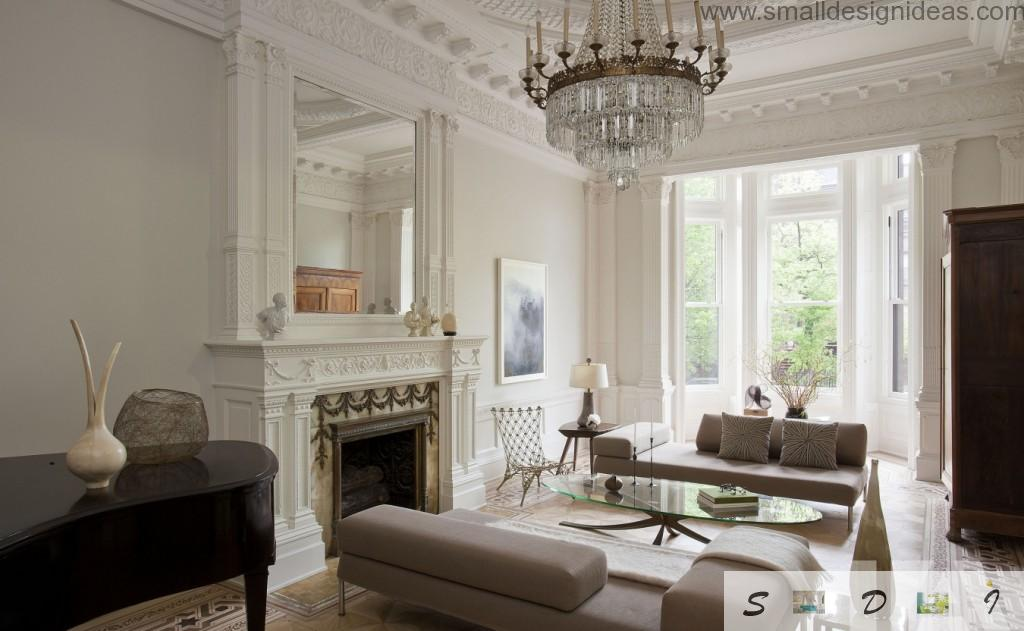 Crystal royal chandelier and the fireplace with big mirror above in the classic living room interior