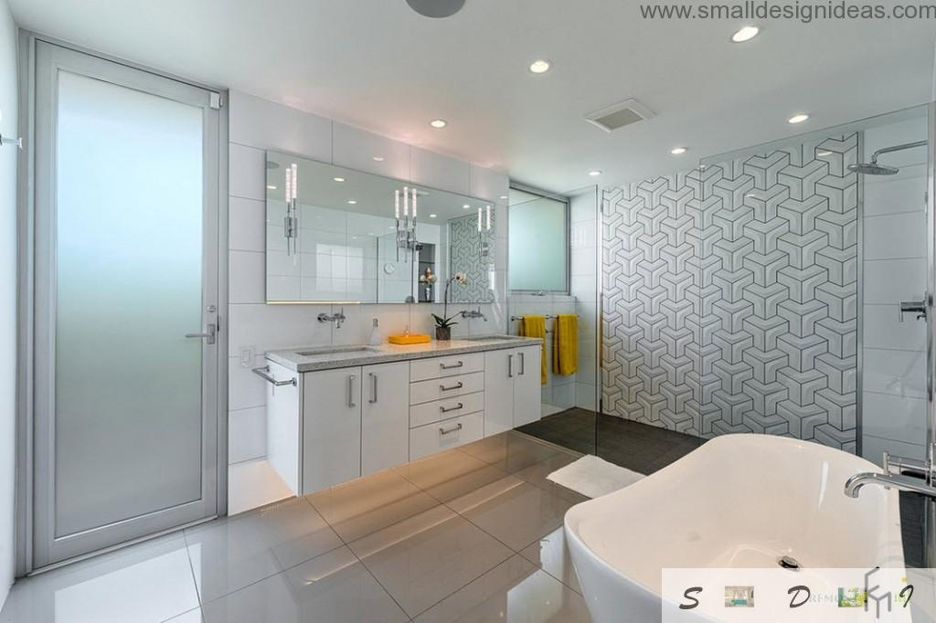 Glass door to the bathroom and white glossy drawers with gray countertop above in the bathroom