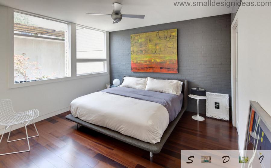 Gray painted brickwork and a picture at the wall of the modern bedroom