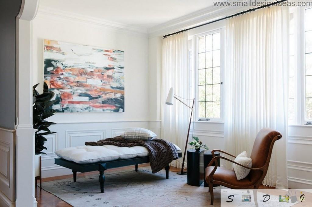 Nice black upholstered sofa on wooden legs and impressionistic picture in the light interior of the living room