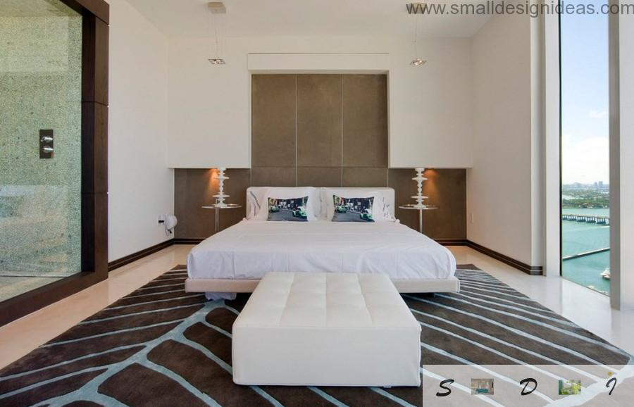 Bed and the ottoman in the spacious badroom of mixed style