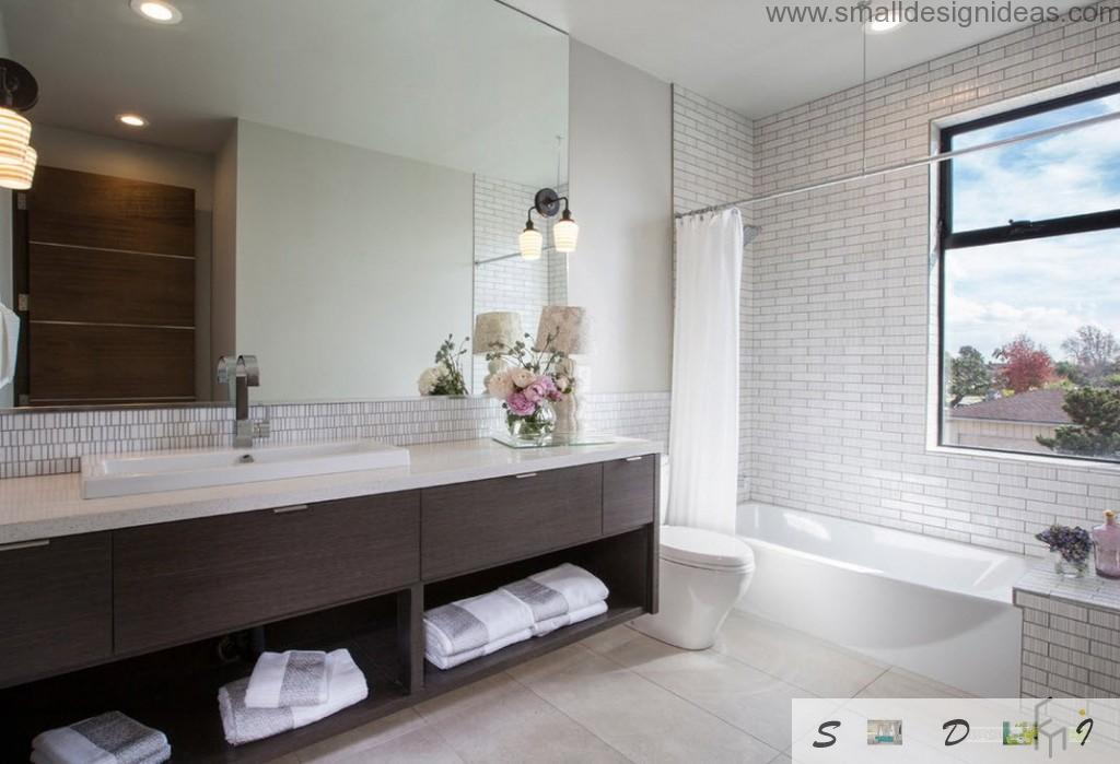 Combined lighting, combined wall trim and wooden furniture makes the ambience in light bathroom