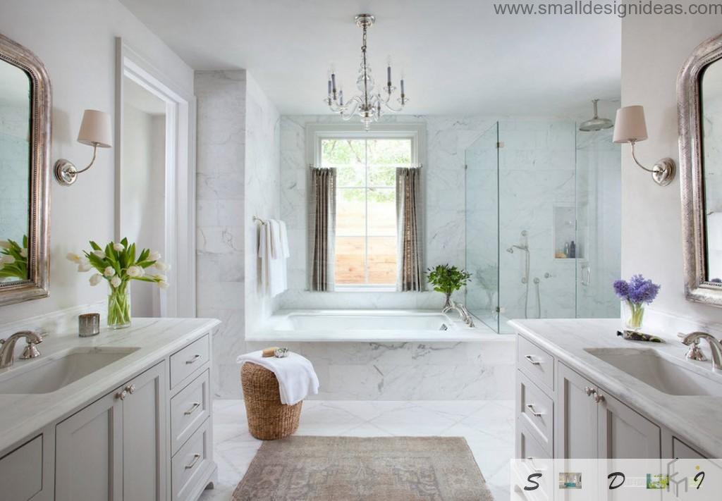 Bathroom with rwo sinks at different walls and a bathroom in center with marble trim