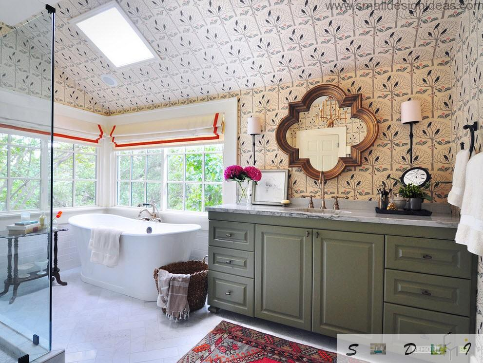 Attic bathroom with ceiling window and mirror above the wooden greenish chest of drawers
