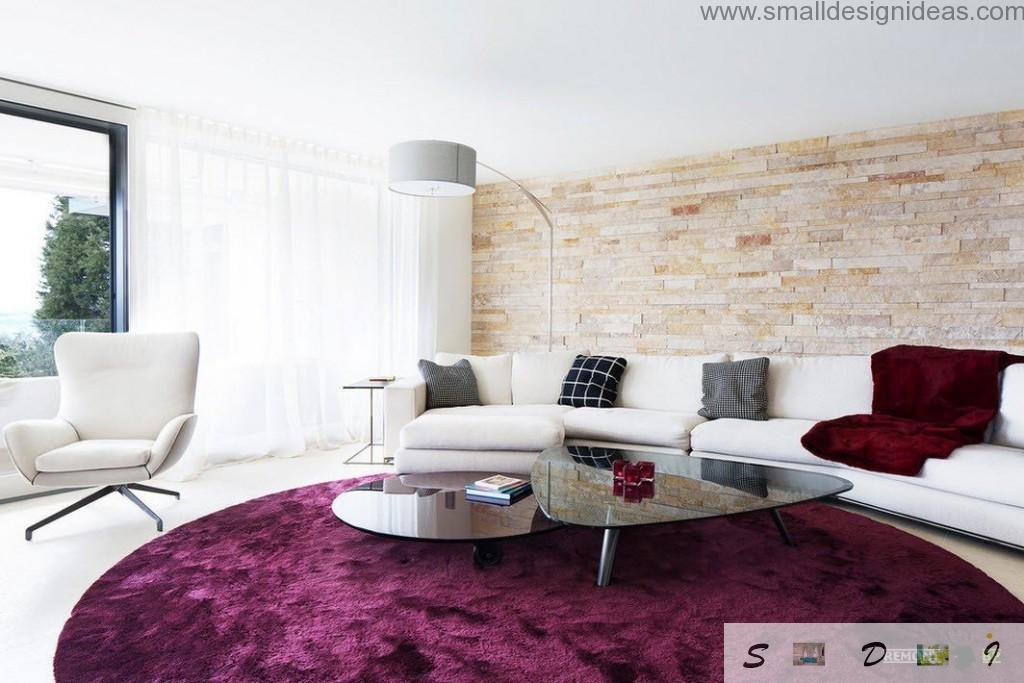 Purple carpet in the light living room interior with upholstered furniture and glass coffee table