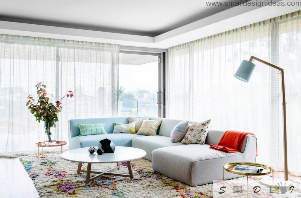 White and dotted cuchoins in the upholstered angle sofa in the spacious living room with panoramic windows and stand lamp