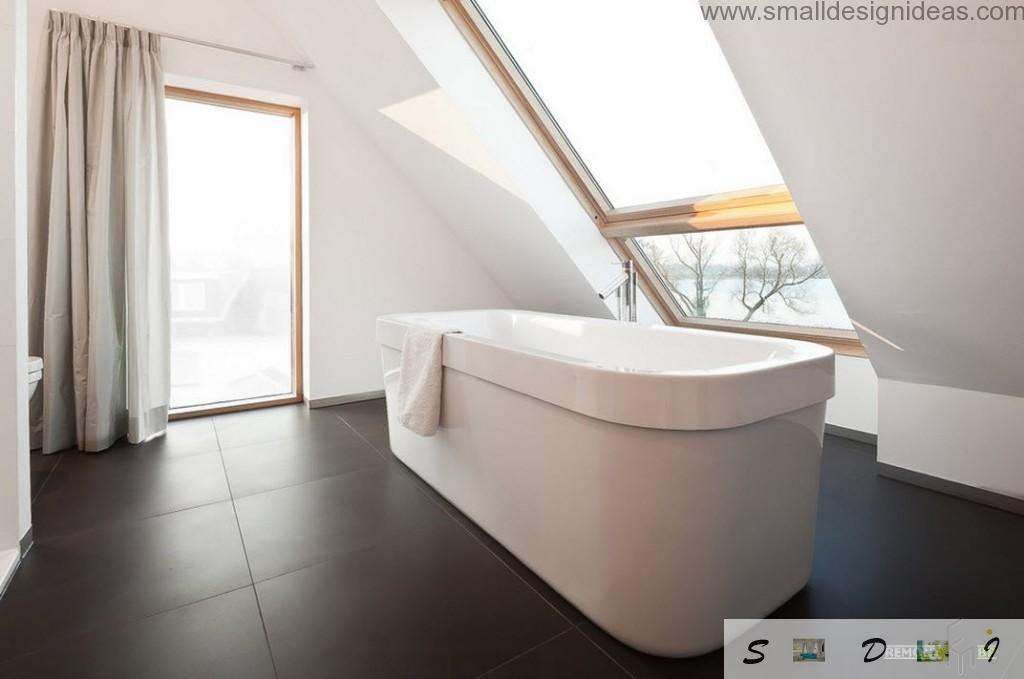 Oval austere bathroom in the contrasting black and white interior of the bathroom with the sloped ceiling and the top window