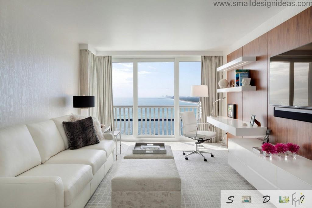 Panoramic window in the creamy colors decorated living room if the seaside house