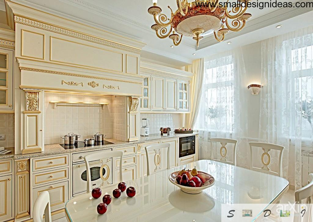Enpire kitchen in all white with golden inlays and chic chandelier of medieval design. Wide windows finishing the image of luxury