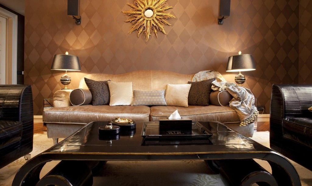 Dark creamy tones in the decoration of the Art Deco living room with a lot of cushions on the couch