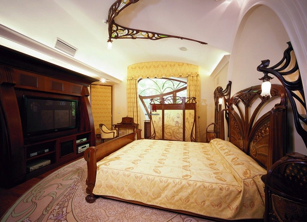 Bedroom styled in the Art Nouveau style. Carved wooden bed, wooden crown in the ceiling and unusual furniture