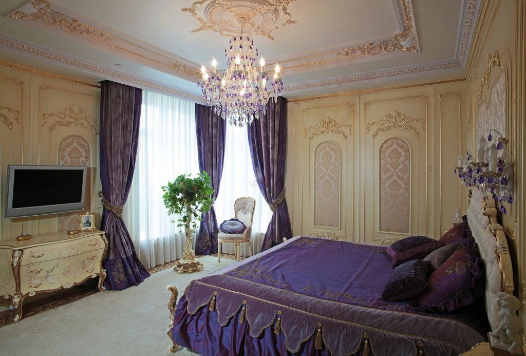 Baroque purple colored bedroom with gilded ceiling stucco and crystal chandelier
