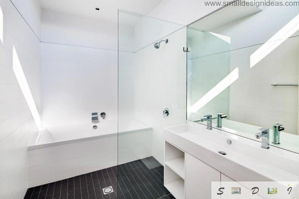 Contrasting black tiled floor in the spotless white bathroom interior