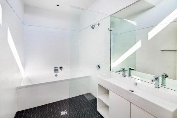 Contrasting black tiled floor in the spotless white bathroom interior
