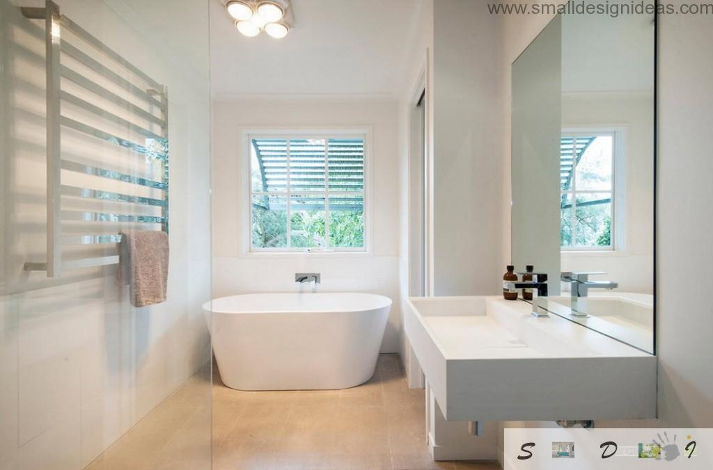 Oval unique bathtub in the plastered white bathroom