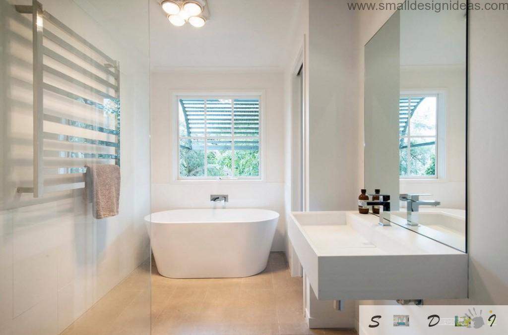 Oval unique bathtub in the plastered white bathroom