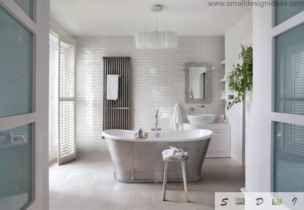 Steel bathtub in the centre of vintage white tiled bathroom interior