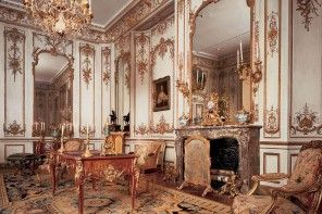 Unique carved handmade Rococo style furniture in spacious high room with fireplace and a huge mirror