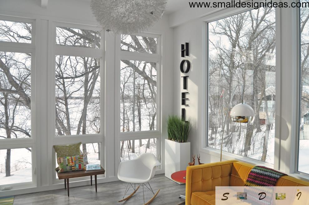 White cold eco living room with huge windows and modest greenery inside
